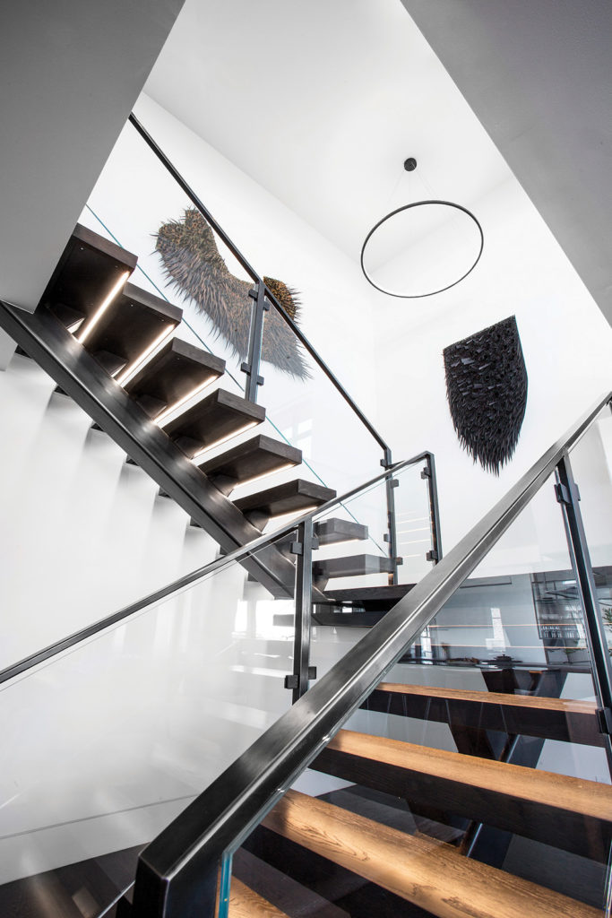 Staircase with floating landing, glass-and-steel railings and open treads