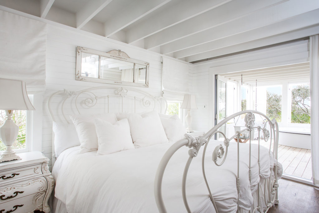white-on-white bedroom, painted iron headboard and footboard, rustic side table