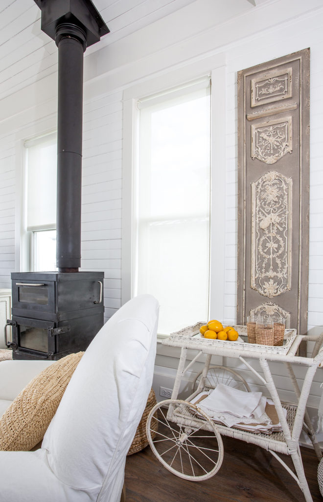 shiplap walls, white-neutral decor, wood-burning fire place, beach cottage