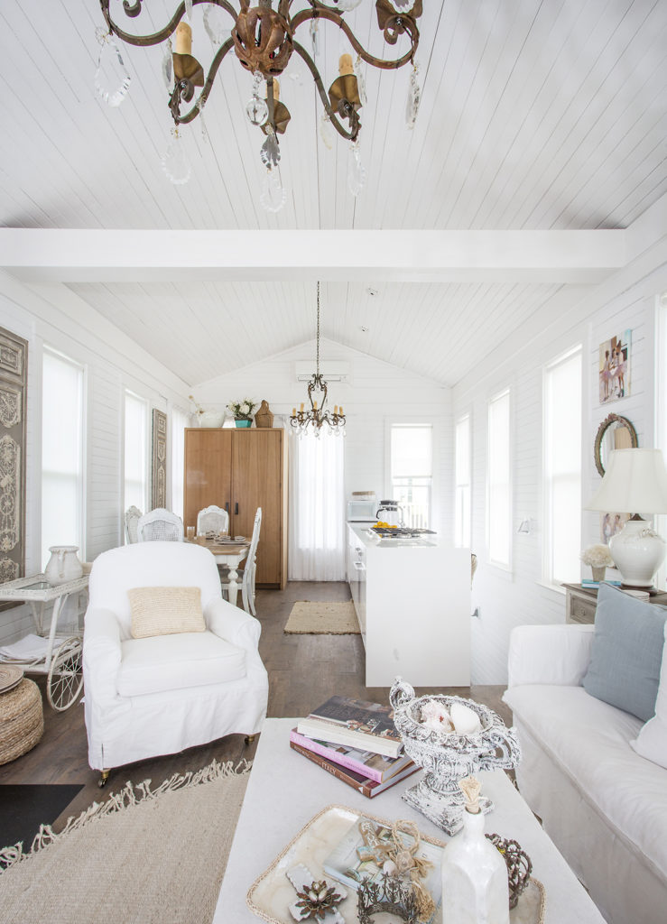 open-planned living room, galley kitchen, antique chandelier, shiplap ceiling