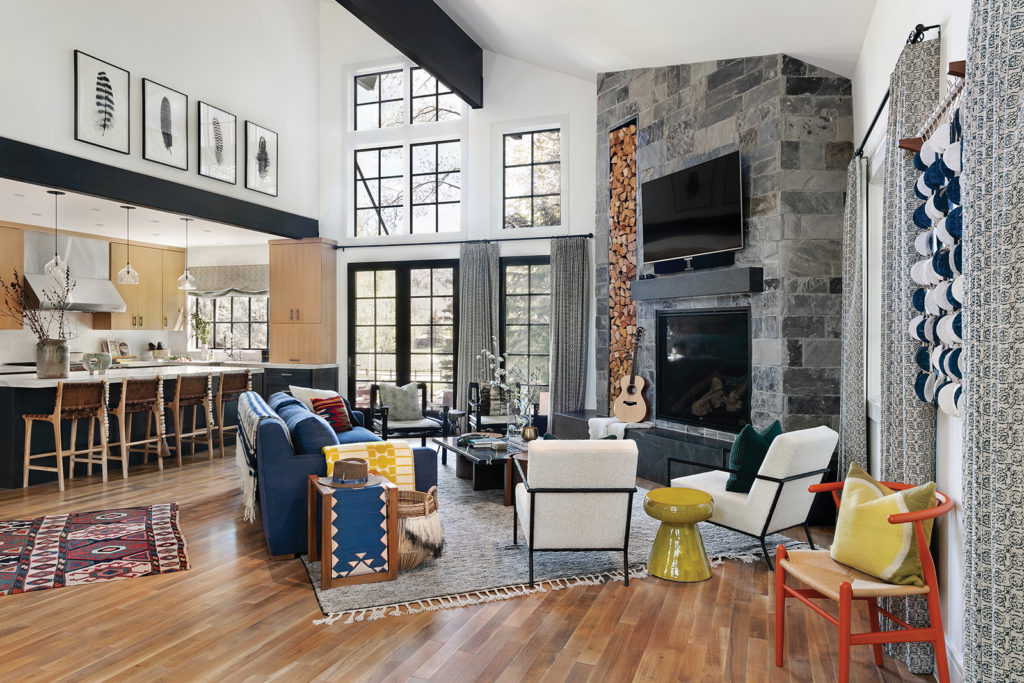 Flairhunter, Hollis Jordyn Interiors, Sherpa chairs, Stacked firewood box, Gray stone fireplace, Upholstery, Textiles, Wood and marble coffee table, Hand-knotted rug