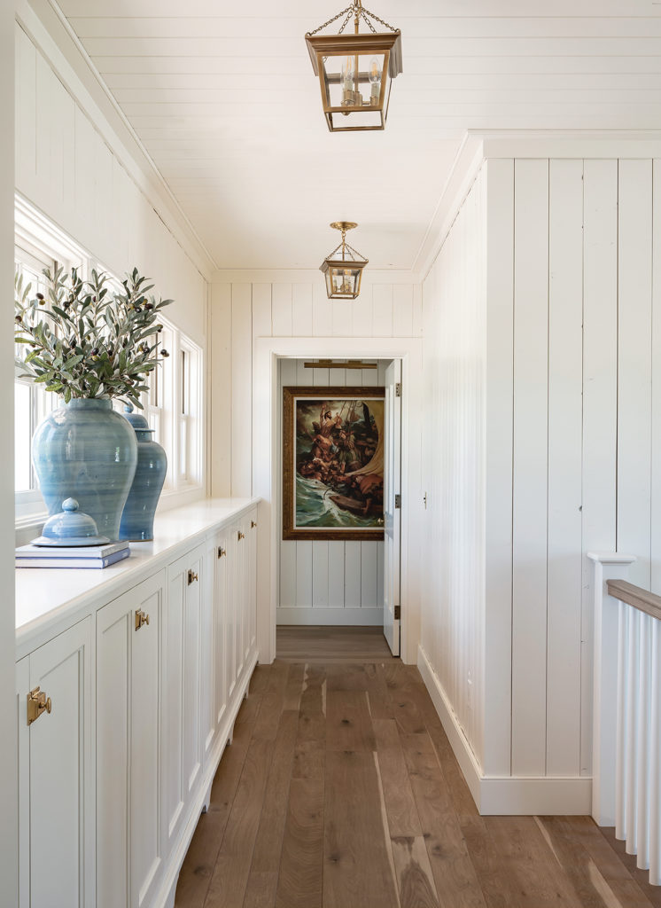 Farm Raised. Brandon Houston, hallway, built-in cabinets, Visual Comfort lanterns, brass hardware, blue plant pots, wood planked walls
