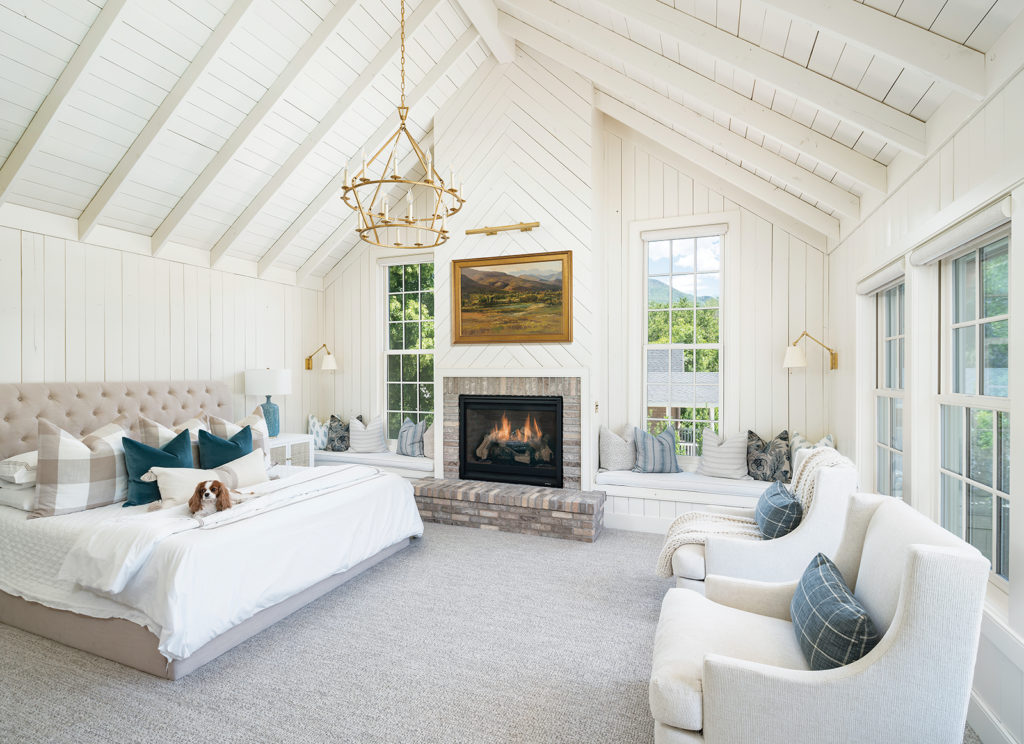 master bedroom, Bodell's, pine slats, exposed rafters, herringbone pattern, brick fireplace,  built-in window seats, tufted upholstered bed, swivel chairs, elegant tiered chandelier, white-gray-blue color scheme