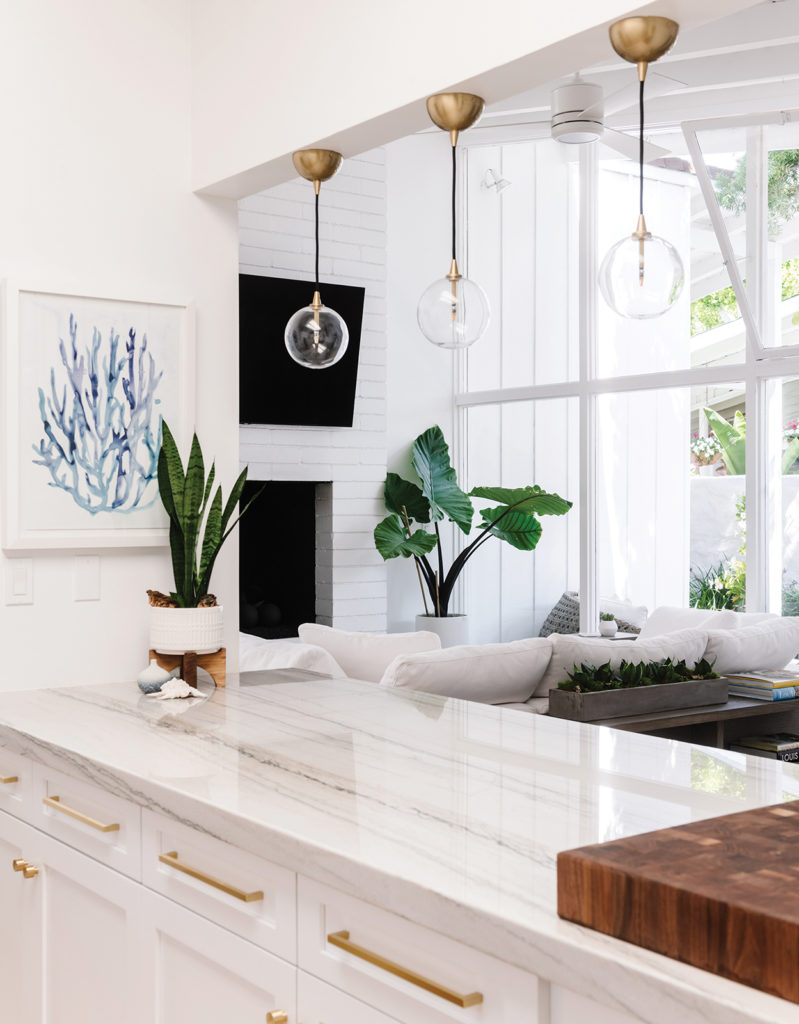 Danielle Hickman designs a White Macaubas quartzite from Venetian Tile & Stone tops new kitchen cabinets. Simple pendant lights from Visual Comfort help promote the room's clean, open design. California Dreaming.