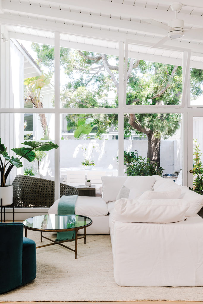 Danielle Hickman Design. Light flows through a wall of windows that connects the living room area to the sundappled patio beyond.