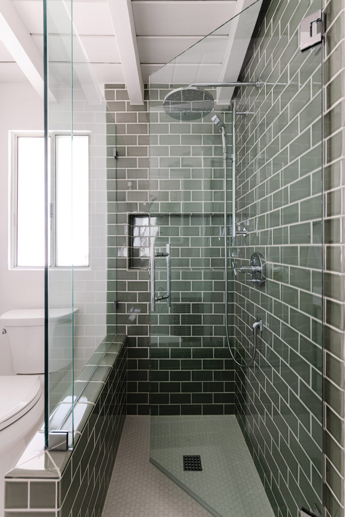 Danielle Hickman Design, Green tile from Contempo Tile invigorates the guest bathroom, where Hickman created a glass shower enclosure to help make the compact space feel open and bright.