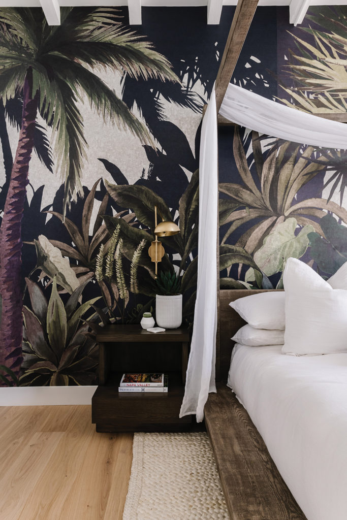 In the master bedroom, Phillip Jeffries' Arboretum mural creates a dramatic backdrop for a large canopy bed draped in a sheer white fabric. Hickman added custom nightstands from Old World Antique Reproductions to fit the compact space and complement its platform bed.