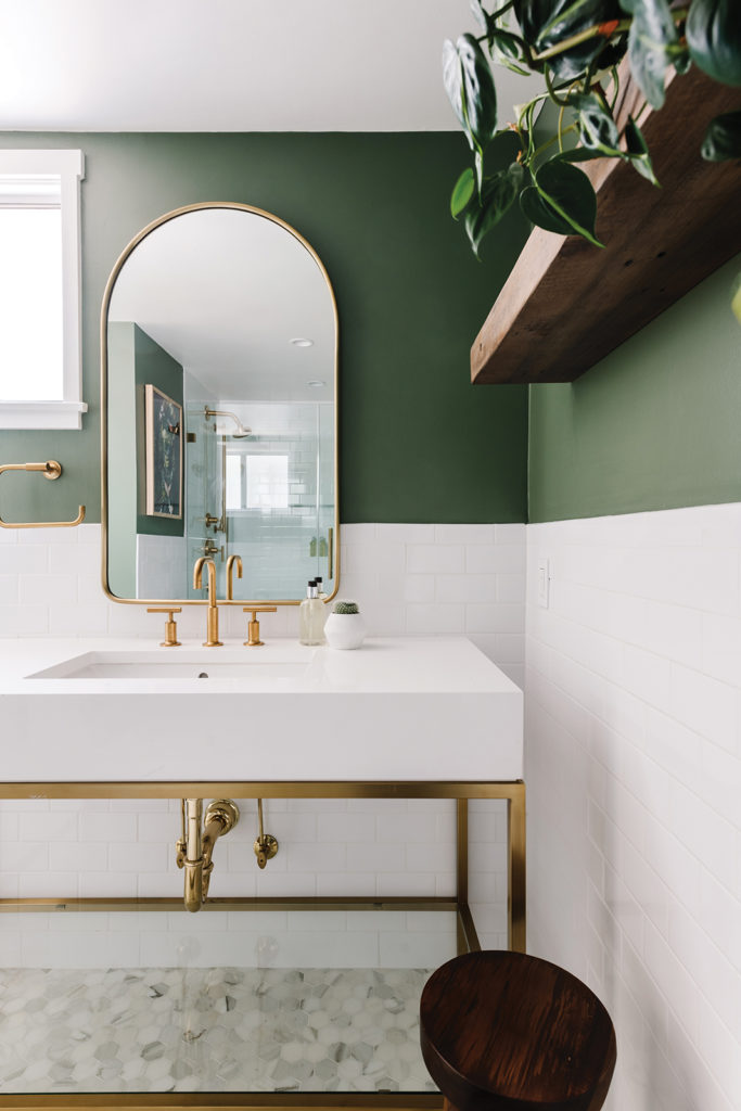 Danielle Hickman designs. Inspired by the bedroom's mural, jungle-green paint enliven's the master bathroom's walls. A brassframed Rejuvenation mirror delivers a shapely reflection of the space.