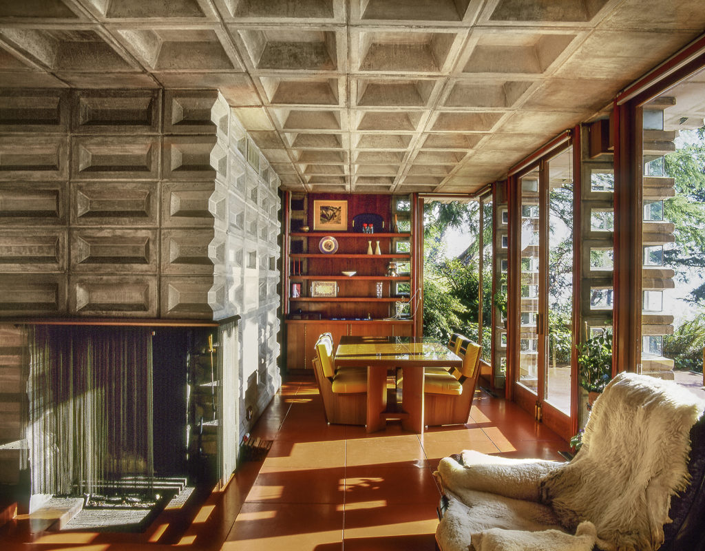 Dining area designed by Frank Lloyd Wright with glass doors and perforated block columns
