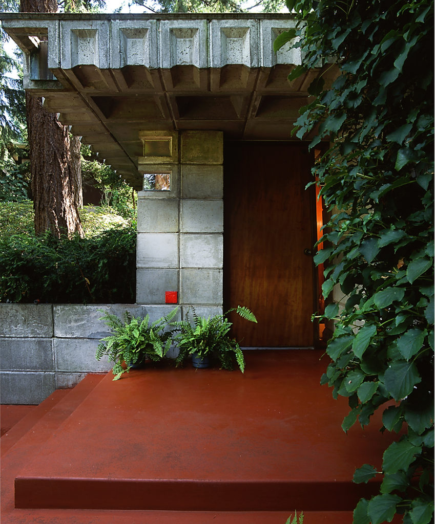 Front door with concrete overhang and red tile