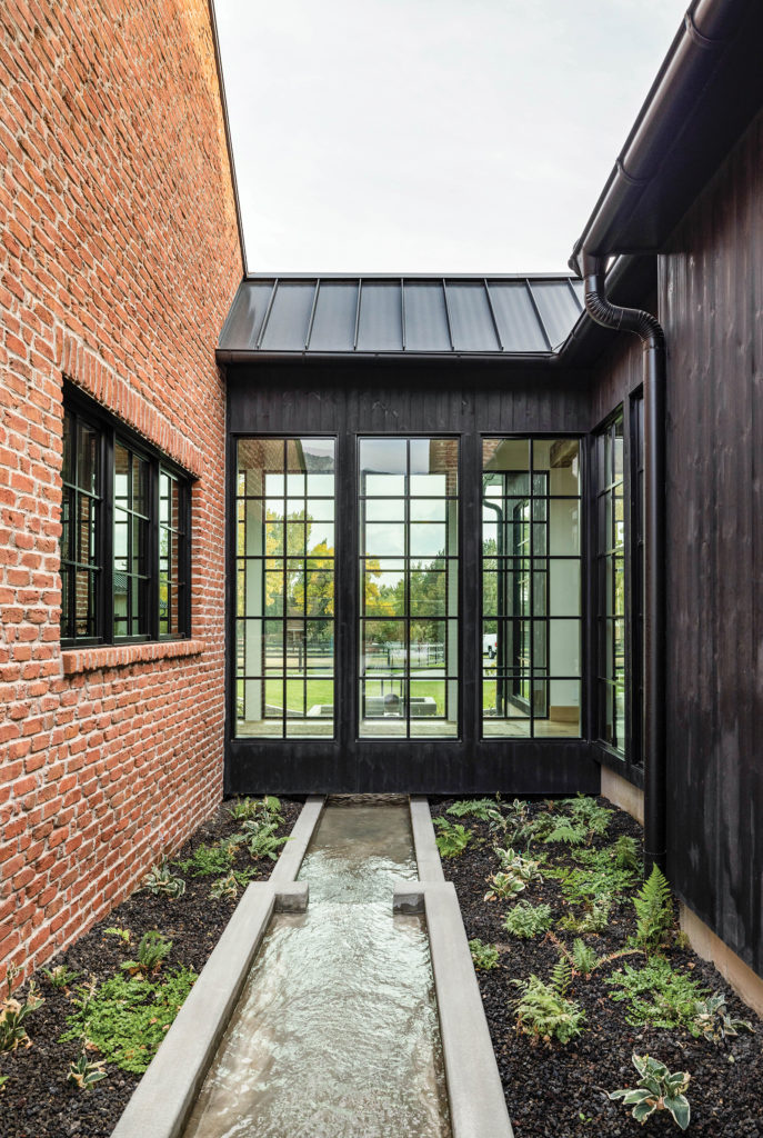 The team at John Martine Studio worked closely with homeowners to create a brick dwelling rooted with farmhouse flair and rustic roots.
